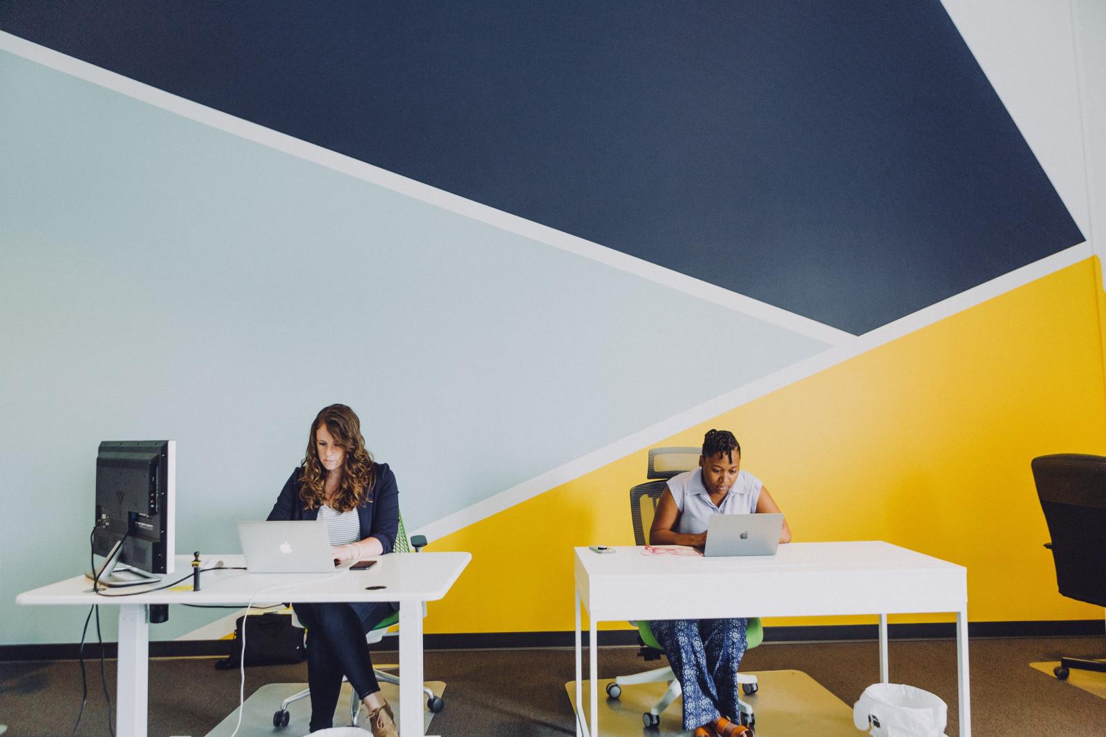 Zwei Damen im Businessoutfit vor einer Wand mit Corporate Colours
